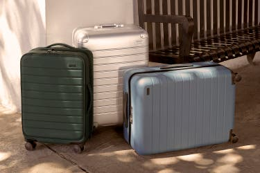 Away luggage, The Expandable softsided carry-on, an aluminum suitcase standing upright, with a hardsided bigger carry-on on its side next to them.