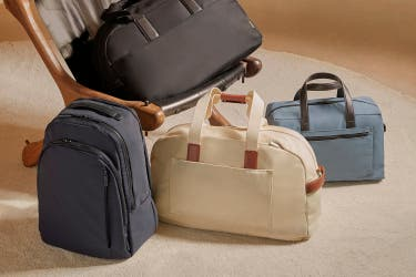 Four travel bags, a blue backpack and three duffle bags in black, canvas and blue for overnight and weekend trips.