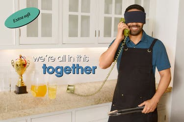 A man wearing an apron and a travel sleep mask talking on a phone in his kitchen.