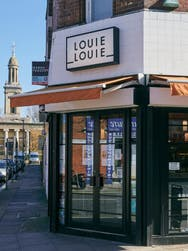 Outside view of the front doors of a retail Store named 'Louie Louie'.