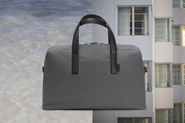 : A duffle bag in grey shown against ocean water on the left and an apartment building on the left.