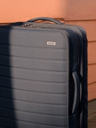 Partial view of an Away grey soft-side carry-on suitcase against a pink background.