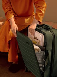 A person wearing orange clothing putting documents into the front pocket a green nylon carry-on suitcase.