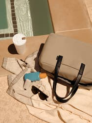 A tan bag next to a pool with a towel, coffee, sunscreen and sunglasses.