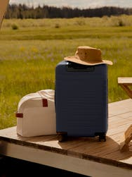 A navy suitcase on a deck next to a sand duffle bag.