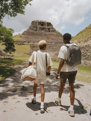 Two friends in Belize carrying an Away backpack in grey and an Away weekender bag in canvas