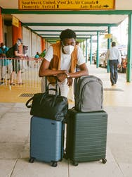 A man in an airport with a coast carry-on and medium green suitcases, a black leather tote and gray backpack.