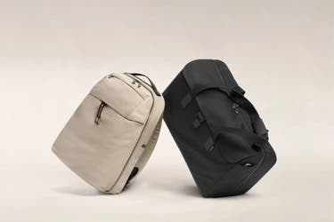 A black Away duffle next to a sand Away backpack.