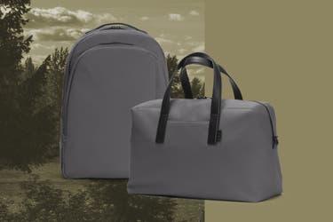 An asphalt Away daypack next to an asphalt Away everywhere bag on a forest inspired background.