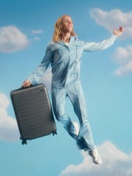 A whimsical man floating through the sky, carrying with him an Away carry on sized travel suitcase