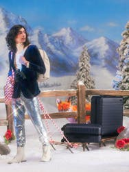 A man in a fictional ski town carrying two Away suitcases in navy on a sled