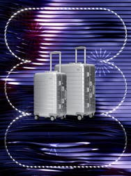 A set of aluminum luggage in checked and carry on sizes overlayed on a sparkly, whimsical backdrop of purple and blue stripes