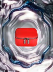A red Away travel Jewelry box overlayed on a whimsical background including silver, purple and blue patterns