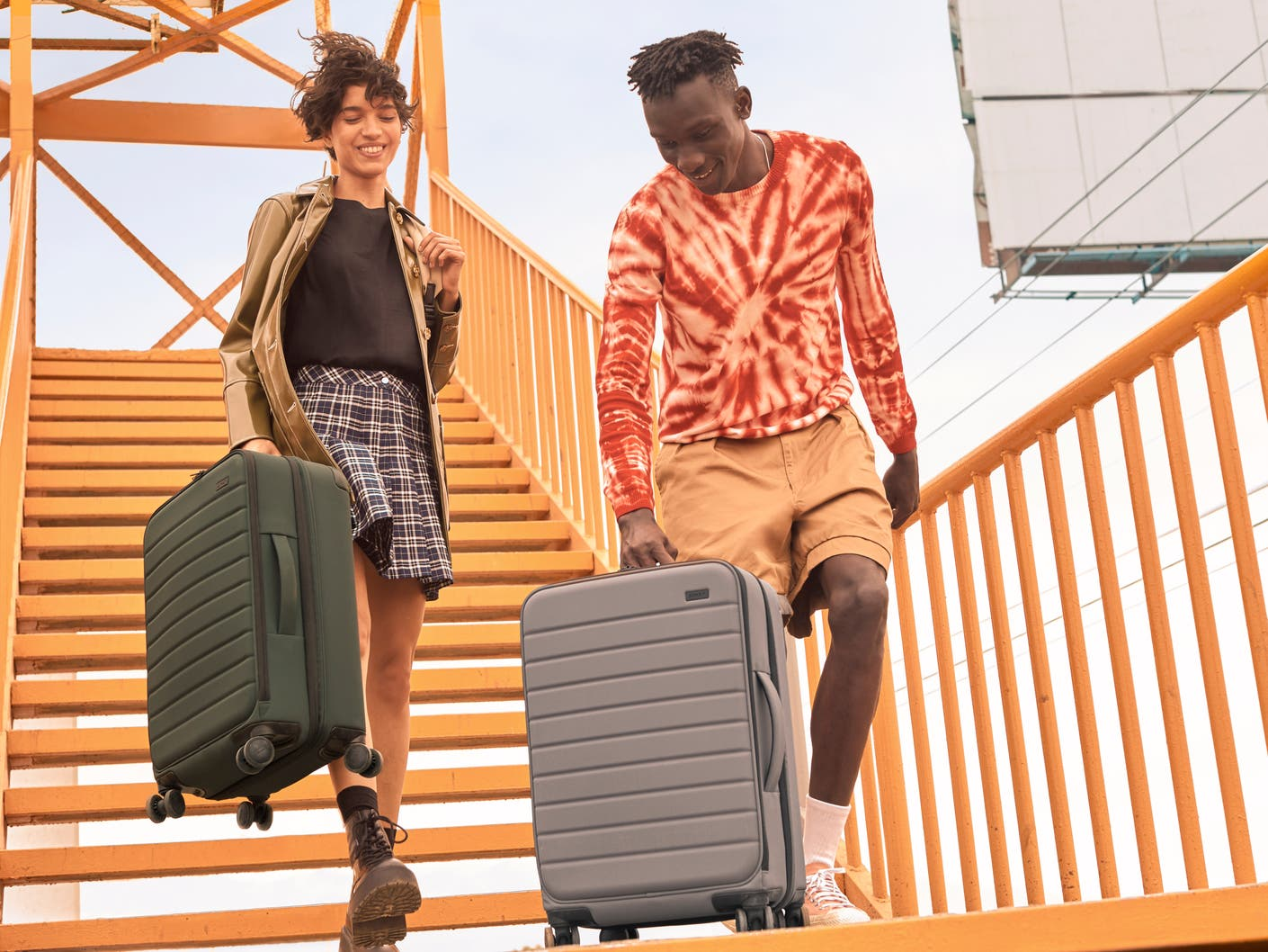 A woman carrying a green suitcase and a man holding a gray suitcase walking down an orange staircase.