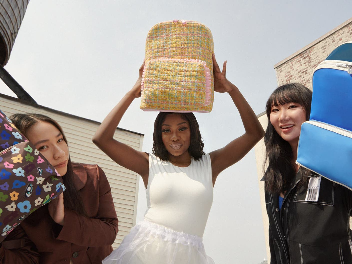 3 Designers, from right to left, Sandy Liang, Tia Adeola and Ji Won Choi, posing with their limited edition Front Pocket Backpacks.