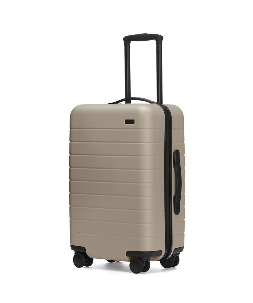 The Carry-On in Sand shown at an angle with raised telescoping handle