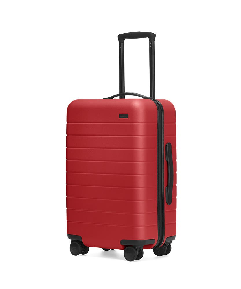 Red hardside Carry-On with raised telescopic handles shown at an angle.