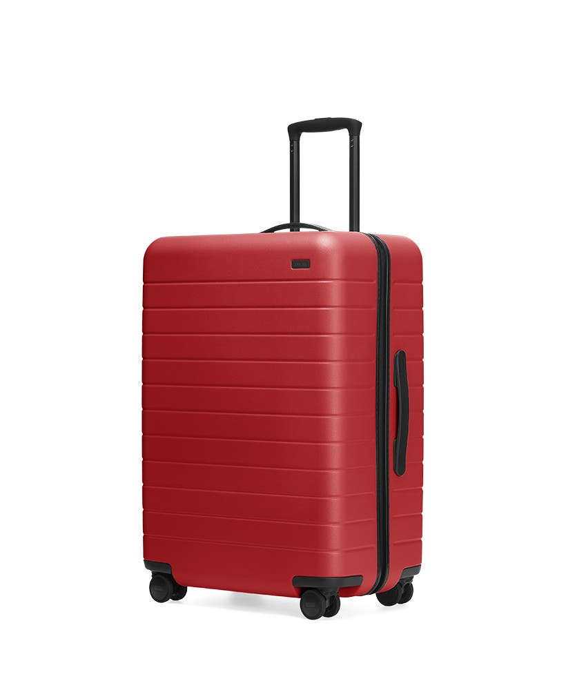 Red hardside Medium with raised telescopic handles shown at an angle.