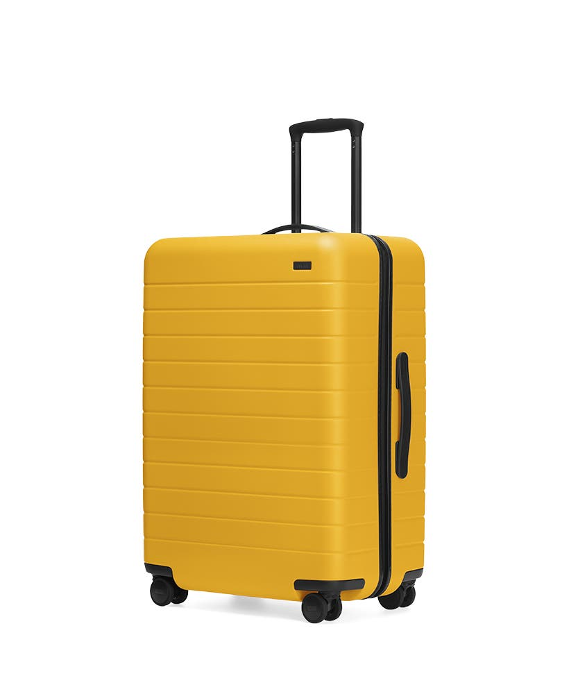 The Canary Medium hardside with raised telescopic handles shown at an angle.