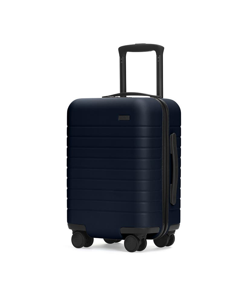The Kids' Carry-On in Navy shown at an angle with raised telescoping handle