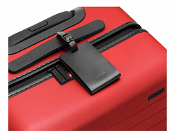 Black leather luggage tag shown on handle of Cherry hard suitcase.
