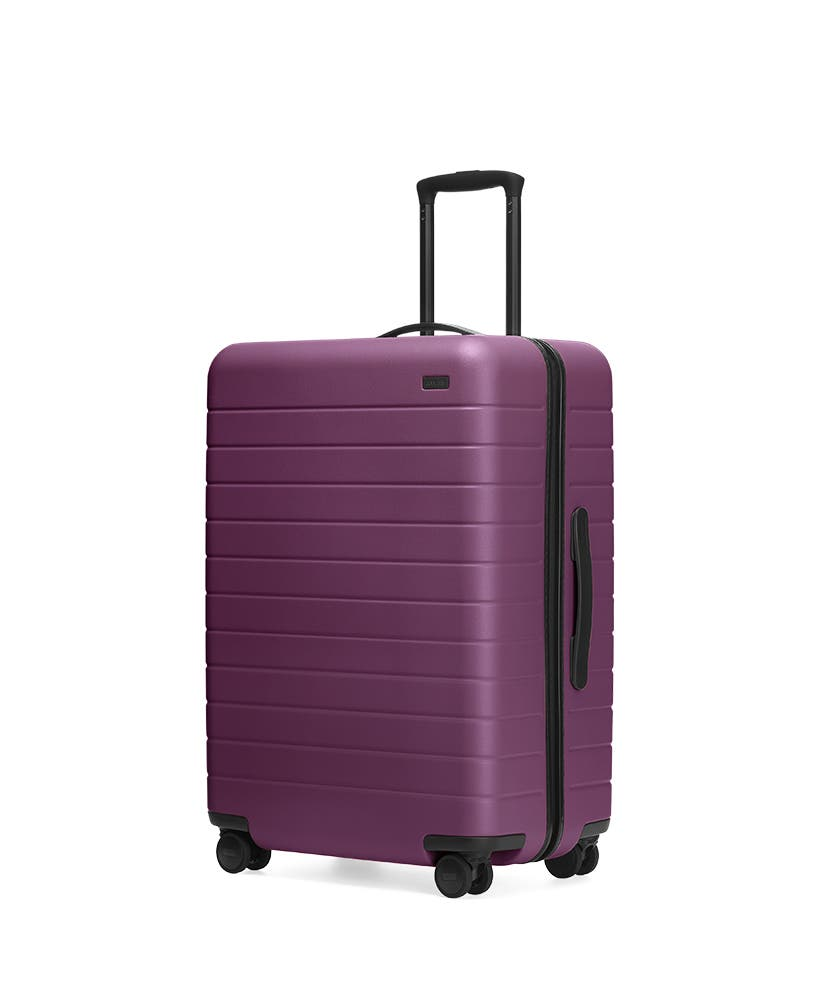 The Plum Medium hardside with raised telescopic handles shown at an angle.