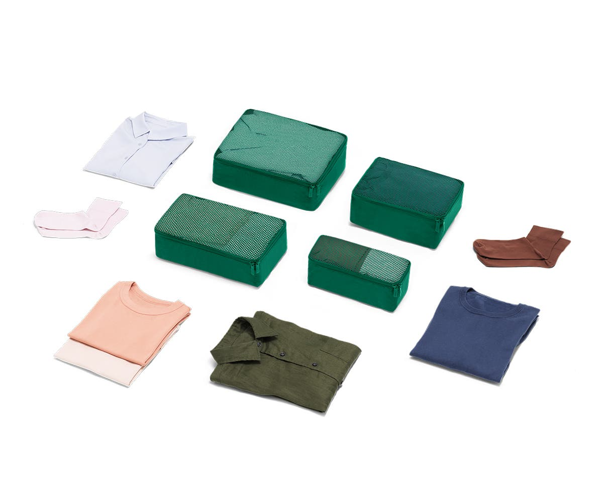 Set of four packing cubes in Sea-green with clothes displayed around it
