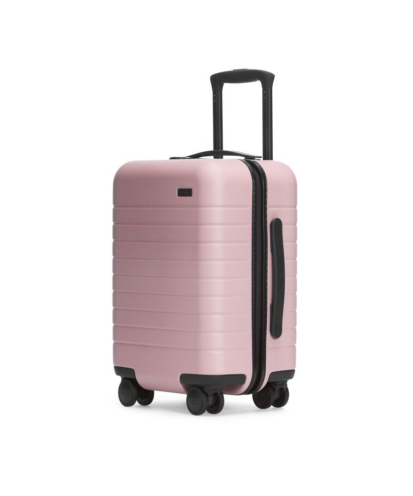 The Kids' Carry-On in Blush shown at an angle with raised telescoping handle