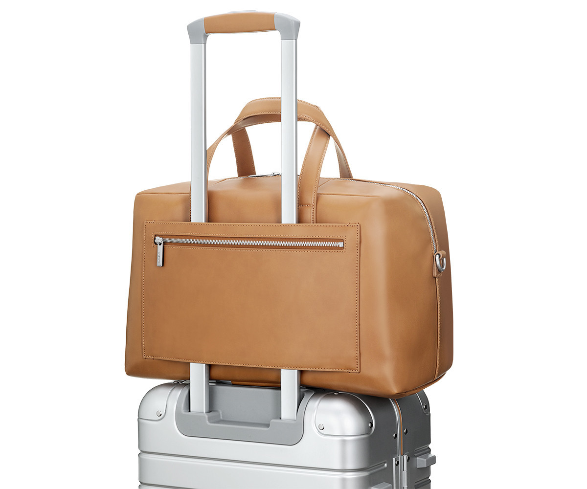 Luggage sleeve shown for a light brown leather duffle strapped to a silver aluminum suitcase with a raised telescopic handle.