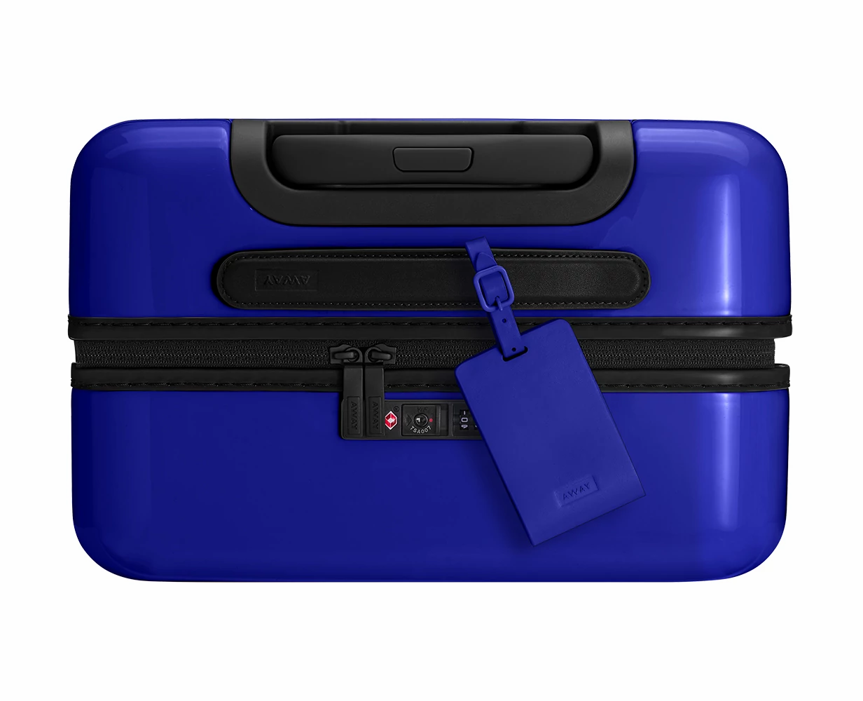 Nightfall leather luggage tag shown on handle of Nightfall Ombre hard suitcase.