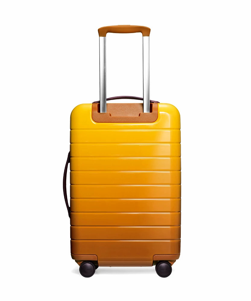 Back view of the Away Golden Ombre Carry-On hardside showing raised handle.