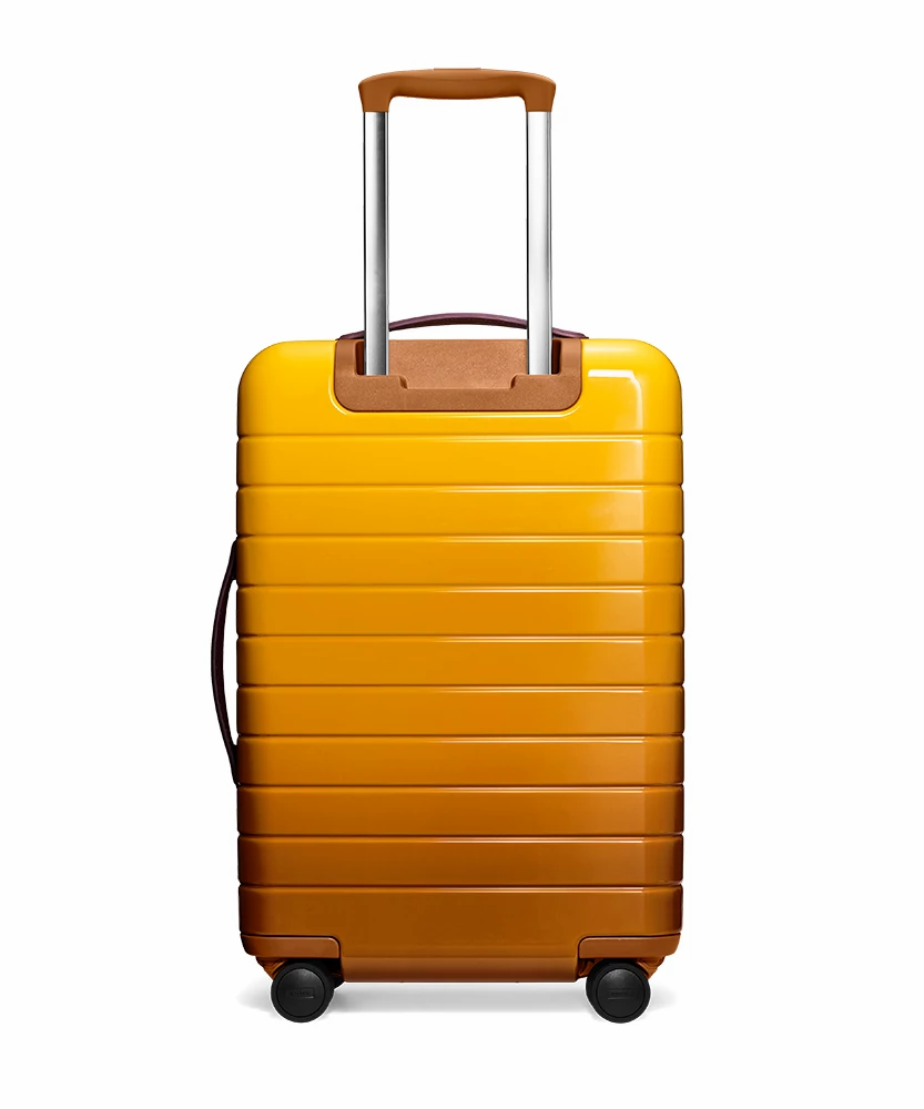 Back view of the Away Golden Ombre Bigger Carry-On hardside showing raised handle.