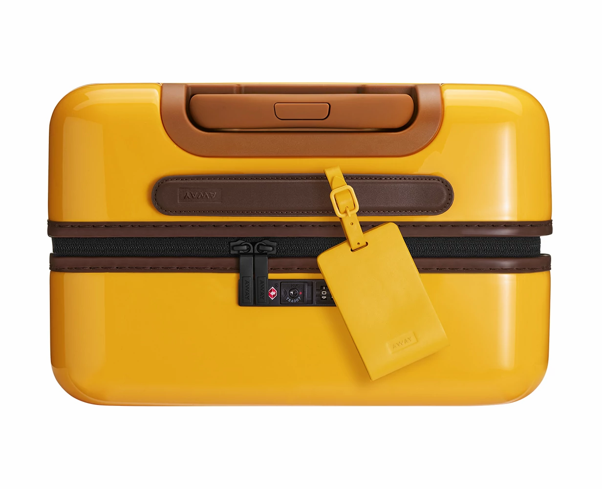 Golden leather luggage tag shown on handle of Golden Ombre hard suitcase.