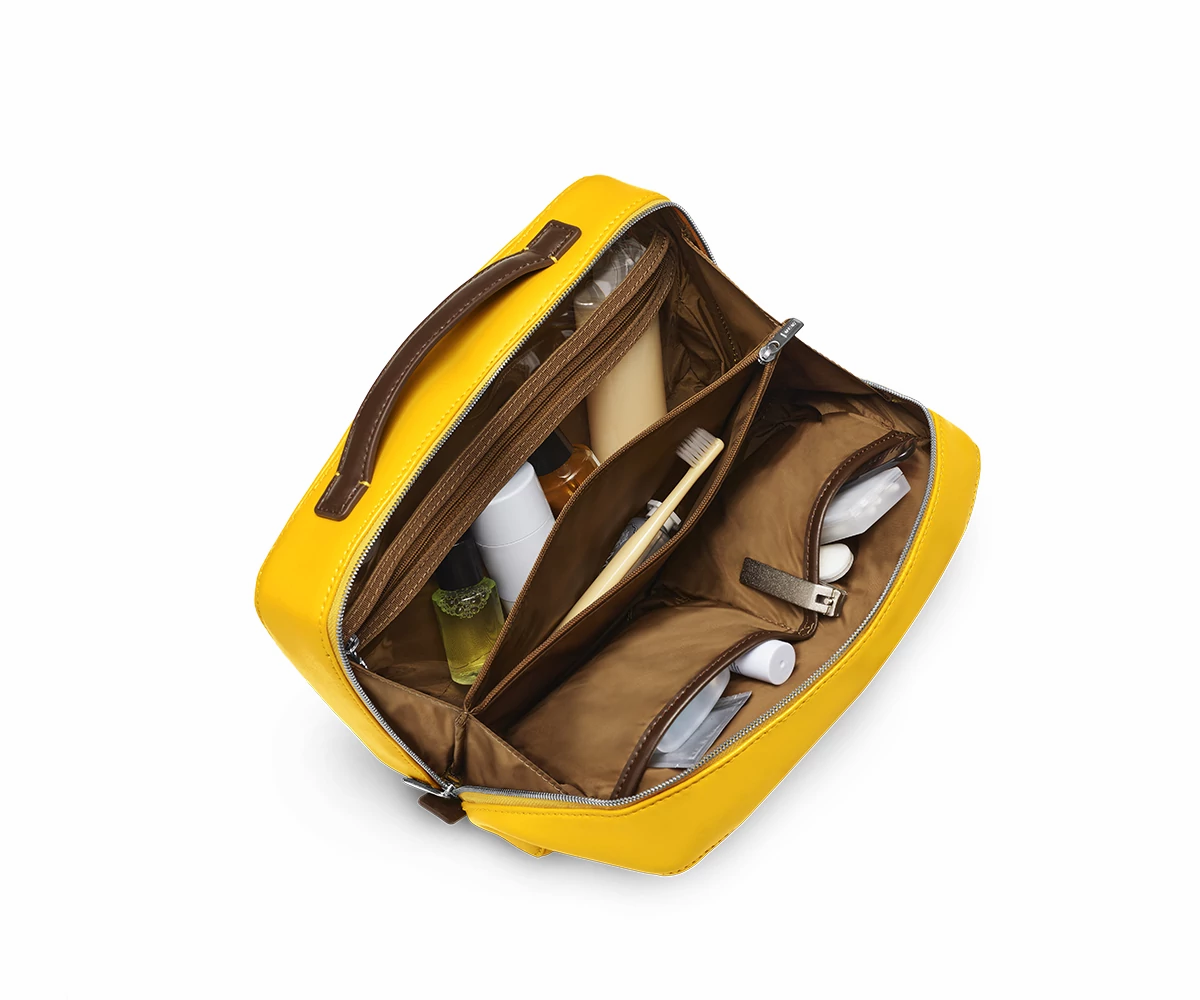 Inside view of a travel toiletry kit in golden yellow with black interior pockets full of travel toiletries.