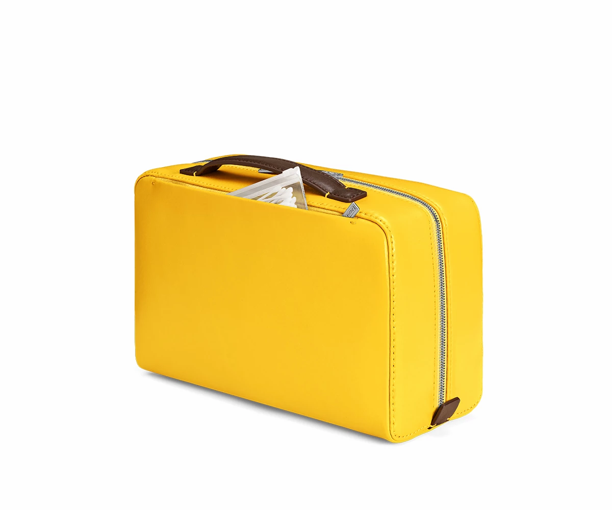 Travel toiletry bag in the color golden yellow with cotton buds in a ziplock bag peeking out of outside pocket.