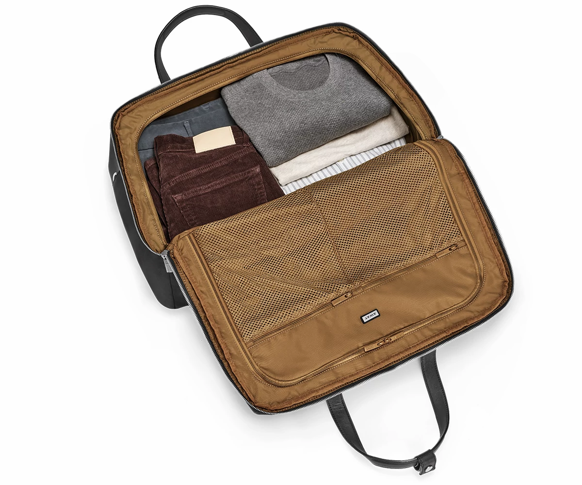 Open large shoulder bag with flap flat and brown interior packed with clothes.