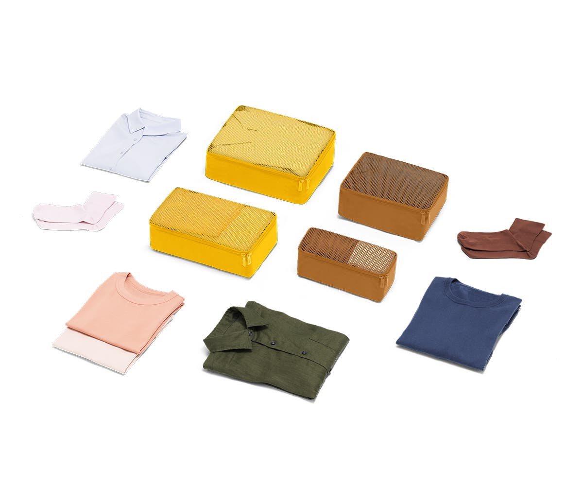 Set of four packing cubes in Golden with clothes displayed around it
