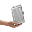 The Away mini suitcase in Silver aluminum balanced in the palm of a hand, tilted on its side