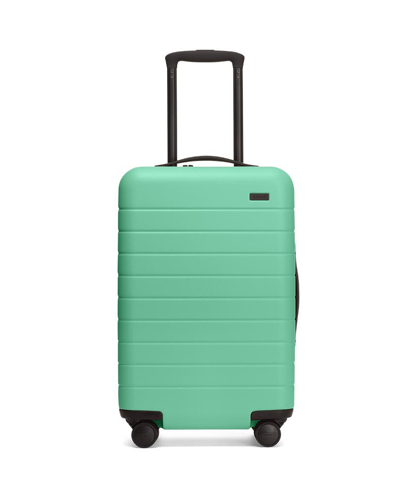 Front view of the Away Aqua Carry-On hardside showing raised handle.