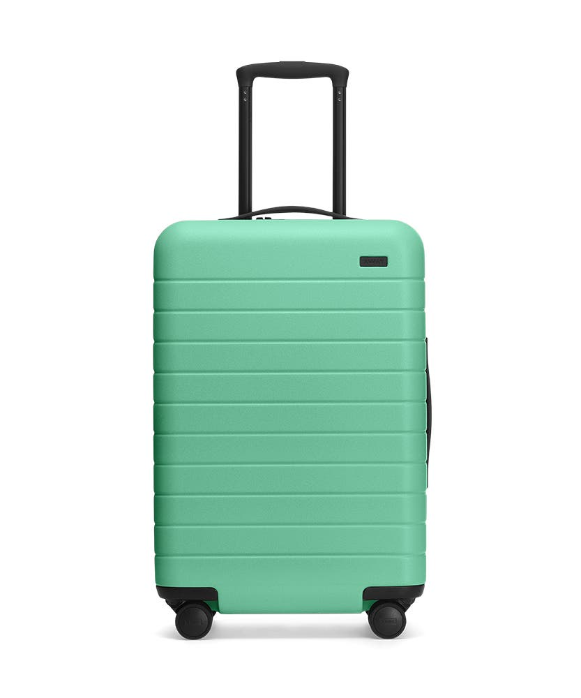 Front view of the Away Aqua Bigger Carry-On hardside showing raised handle.