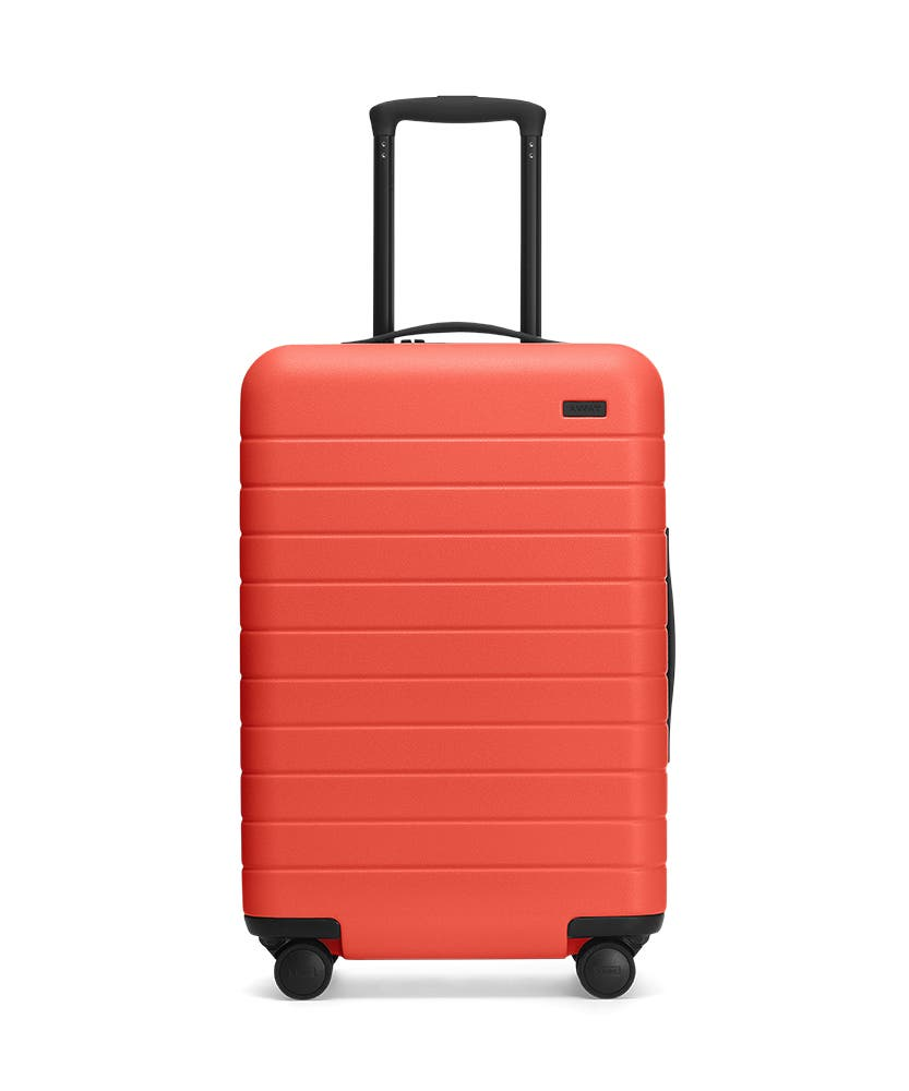 Front view of the Away Coral Bigger Carry-On hardside showing raised handle.