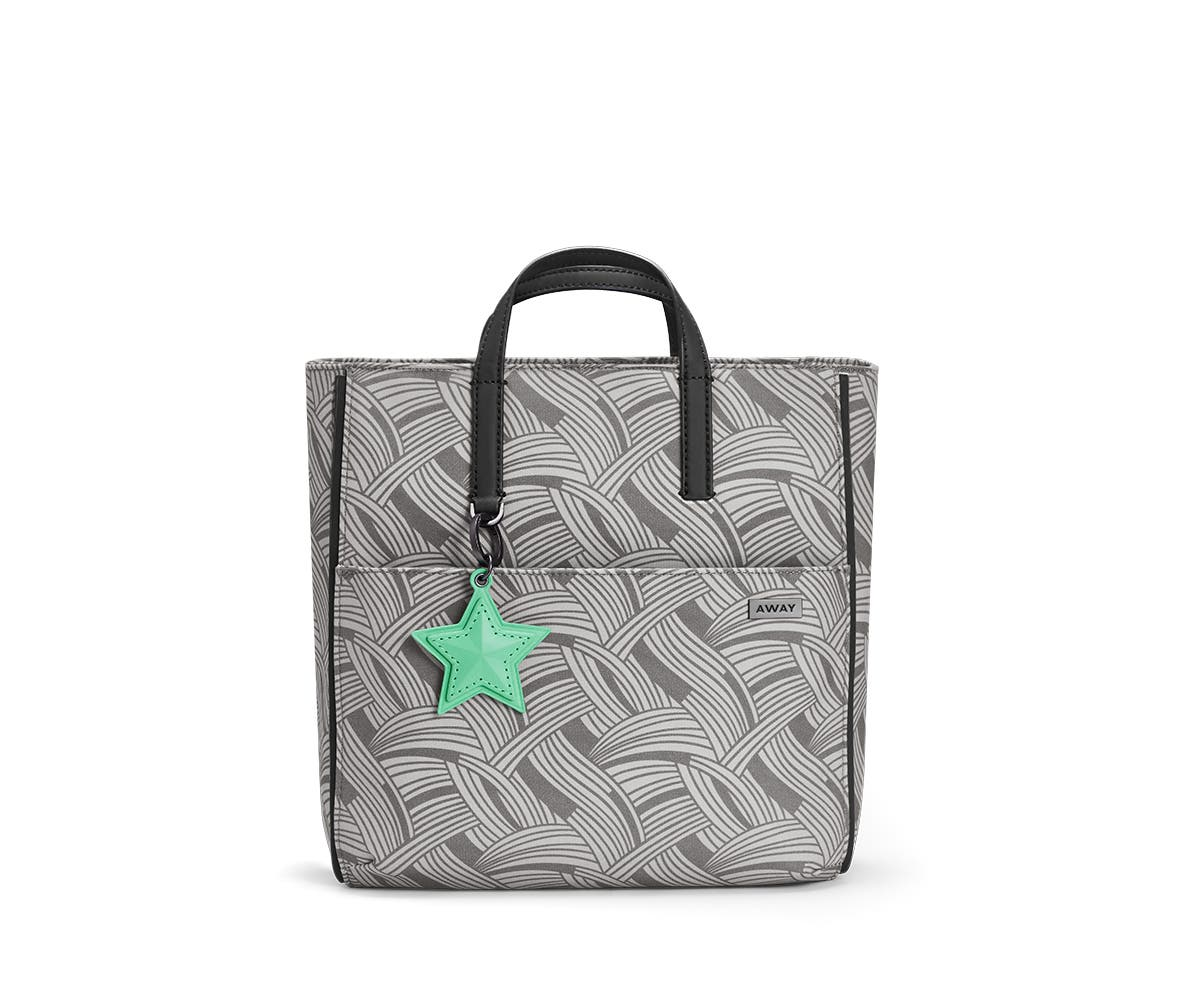 A patterned grey tote shoulder bag with a green star. charm hanging from one end.