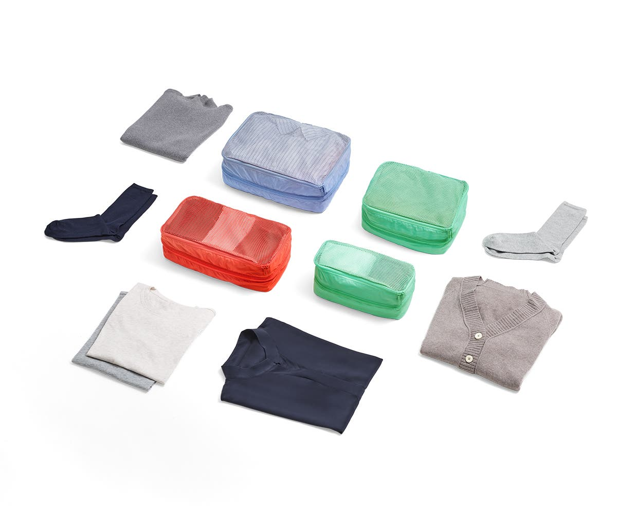 Large and small size packing cubes in red, green and light blue organized with clothing items with carefully folded socks and shirts around them.
