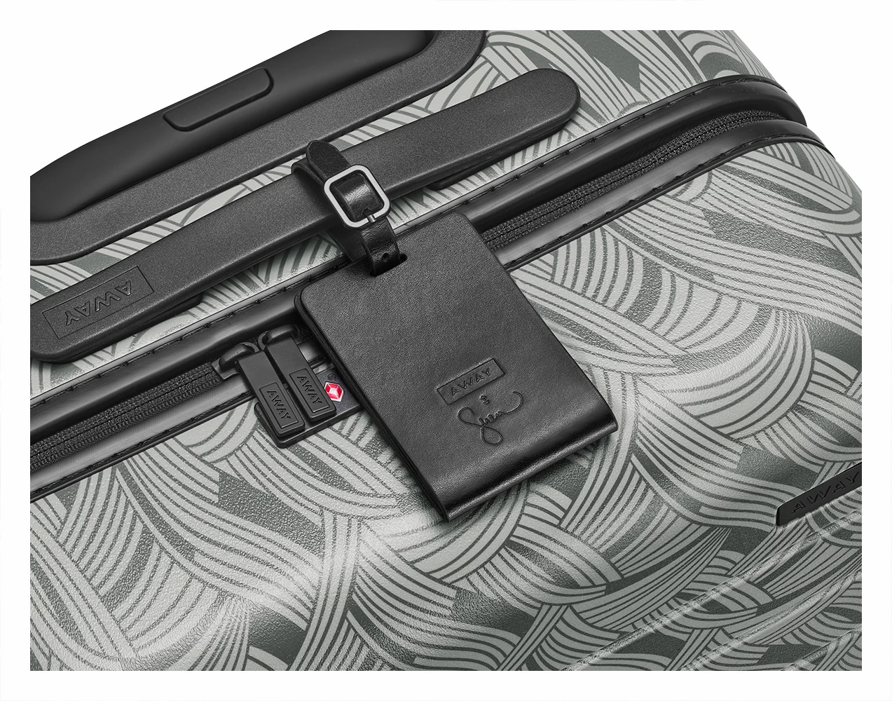 Light-Swirl leather luggage tag shown on handle of Light-Swirl hard suitcase.