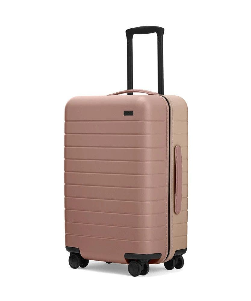 Dusty Rose/ Taupe Bigger Carry-On hardside with raised telescopic handles shown at an angle.