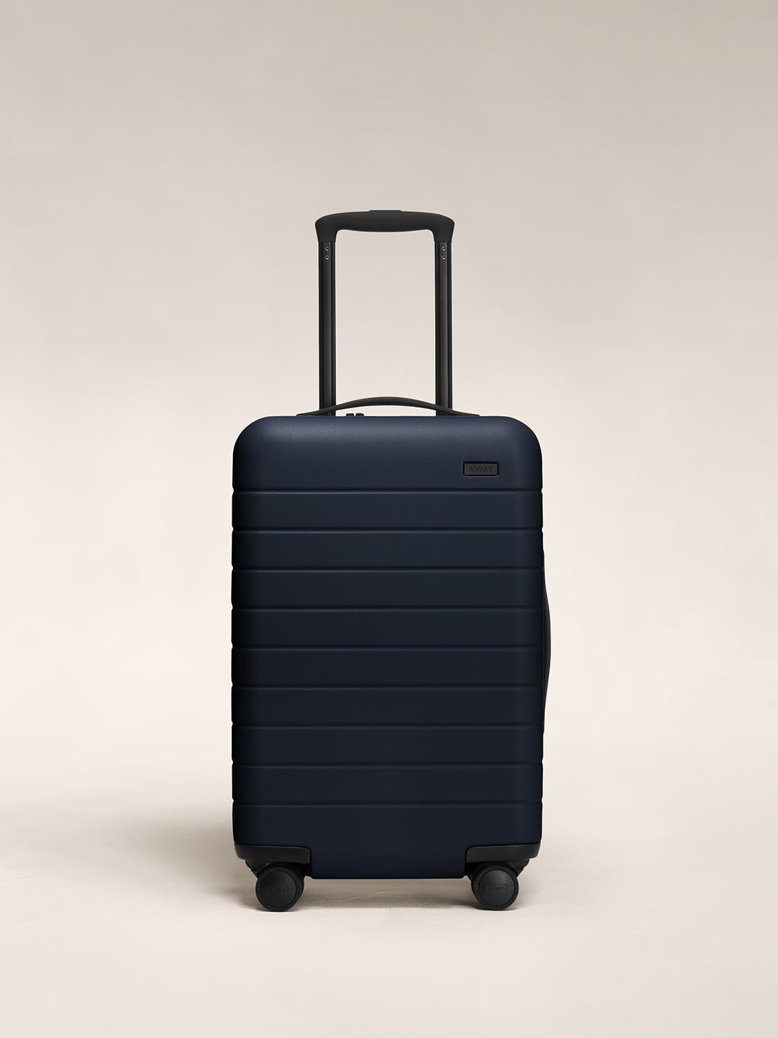 Front view of a navy carry-on suitcase with a hard shell, nylon front pocket, and telescopic handle pulled out.
