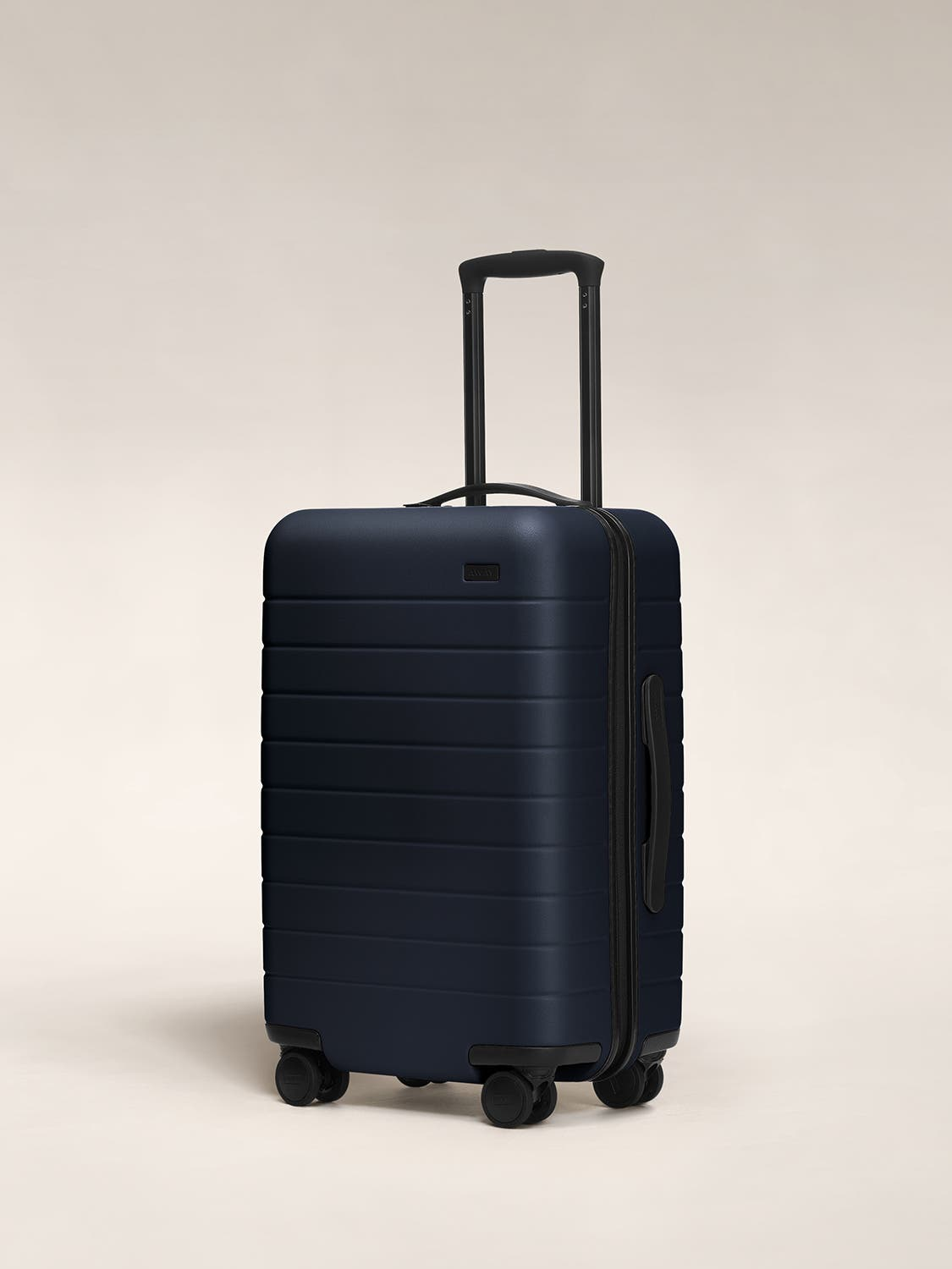 Navy carry-on hardside with raised telescopic handles shown at an angle.