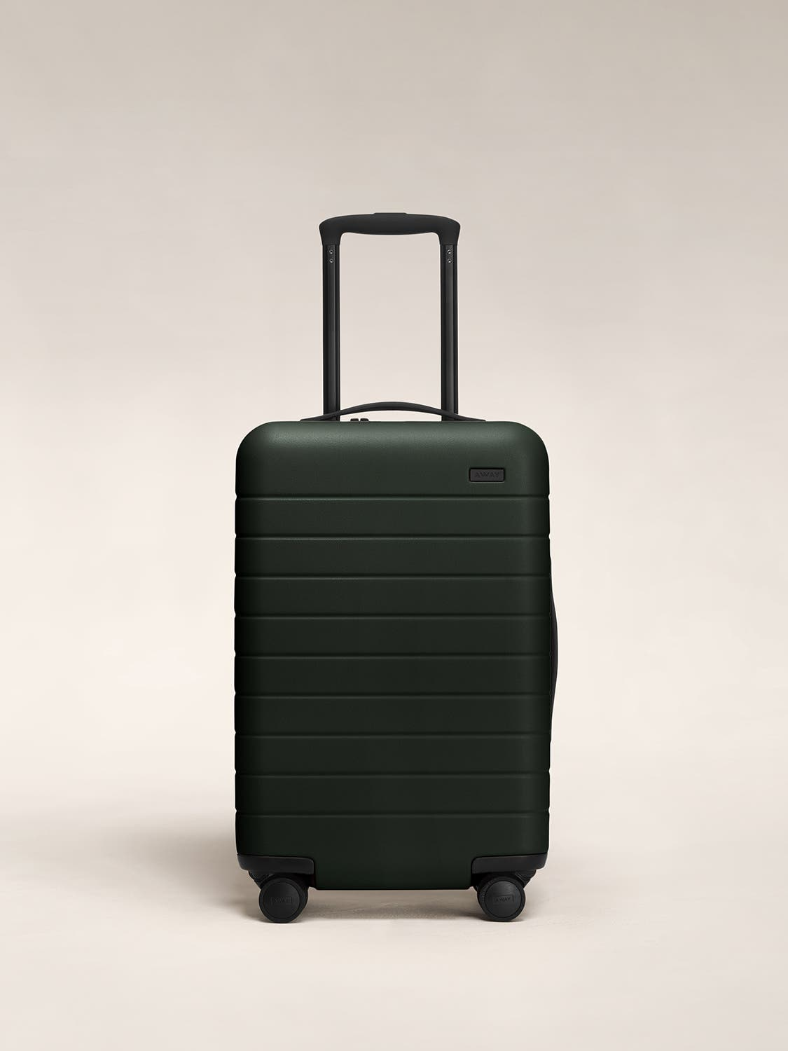 Front view of a green carry-on suitcase with a hard shell, nylon front pocket, and telescopic handle pulled out.