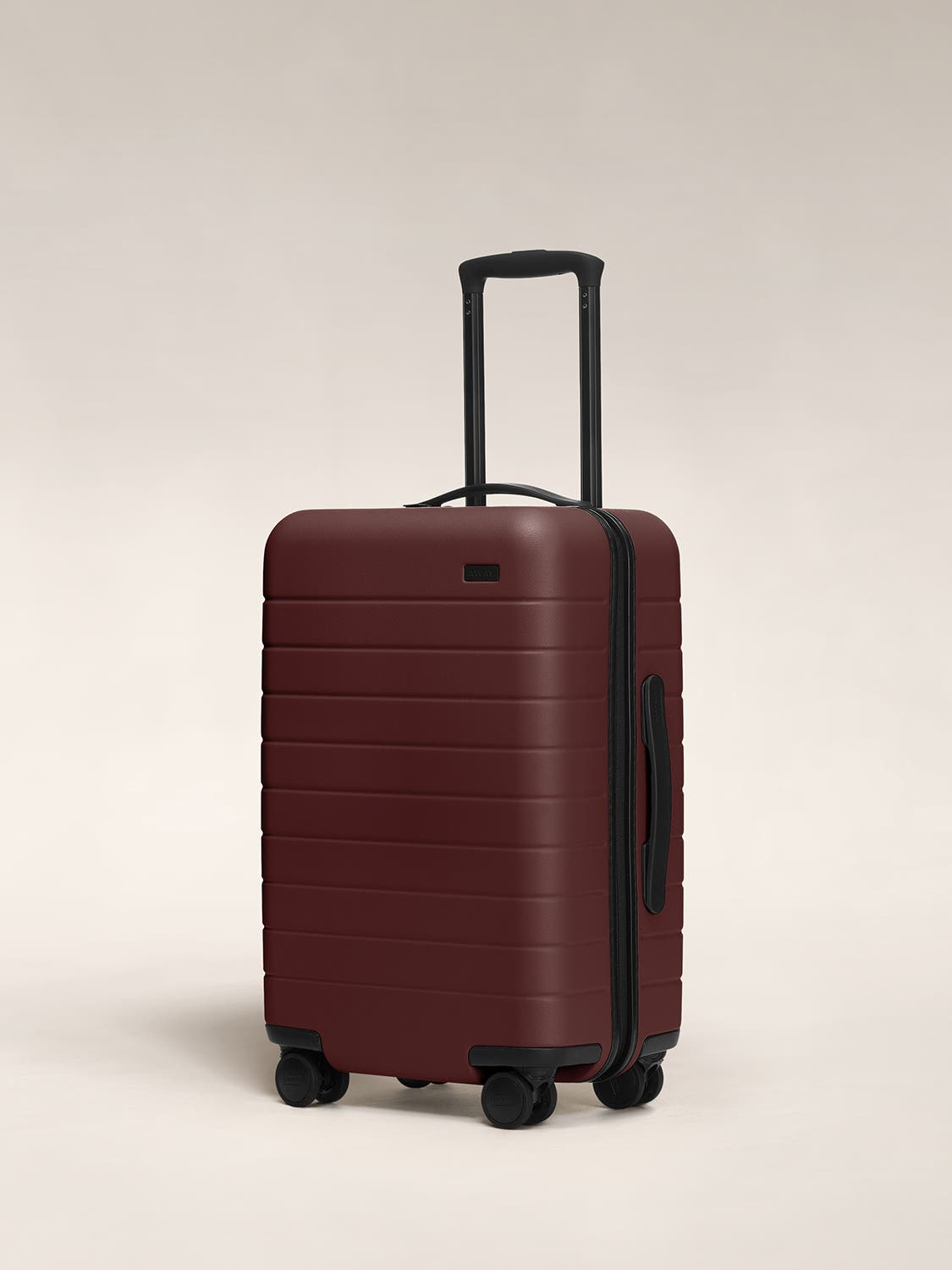 Brick carry-on hardside with raised telescopic handles shown at an angle.