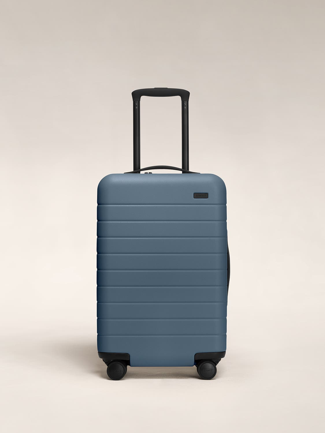 Front view of a coast blue carry-on suitcase with a hard shell, nylon front pocket, and telescopic handle pulled out.